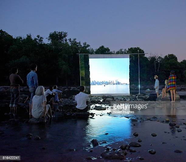 people on river watching movie screen - プロジェクター ストックフォトと画像