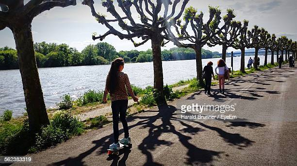People On Road By Trees And River In Park