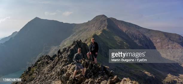 people on rock by mountains against sky - wales stock pictures, royalty-free photos & images