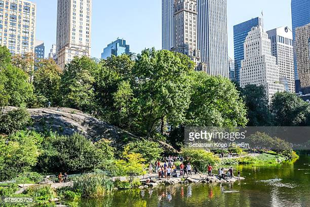 people on rock formation at lakeshore in central park - rock formation stock pictures, royalty-free photos & images