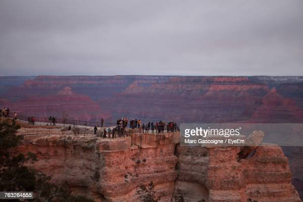 people on rock formations against sky - grand canyon village stock photos and pictures