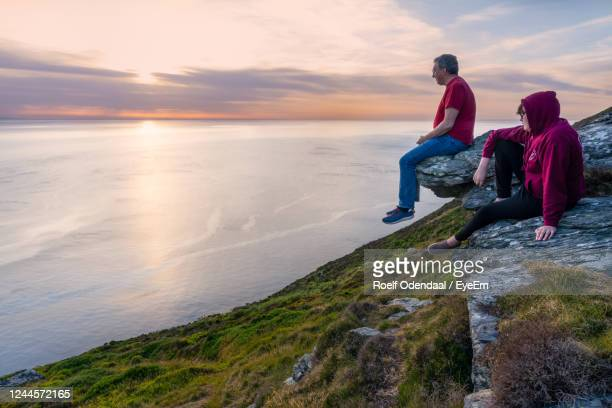 people on rocks by sea against sky during sunset - isle of man stock pictures, royalty-free photos & images