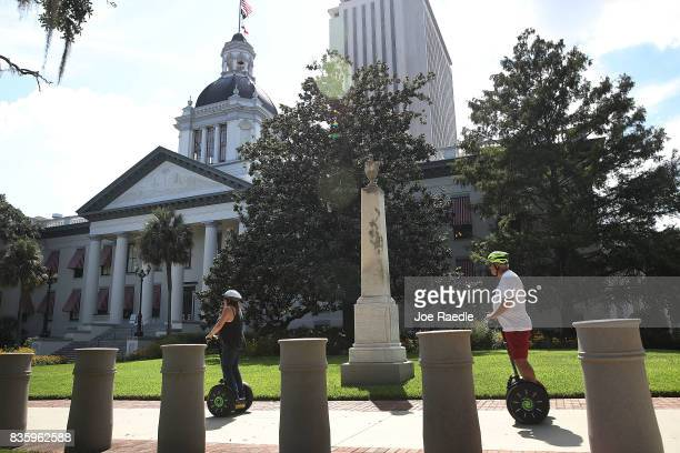People on scooters pass a monument dedicated to Confederate Soldiers from Leon County with the Civil War battles that they participated in listed on...