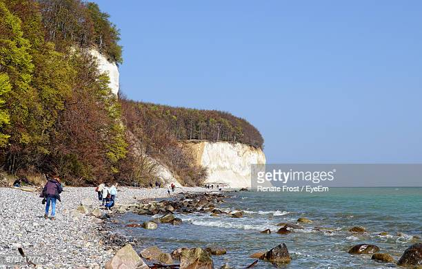 People On Seashore By Chalk Cliff Against Clear Blue Sky