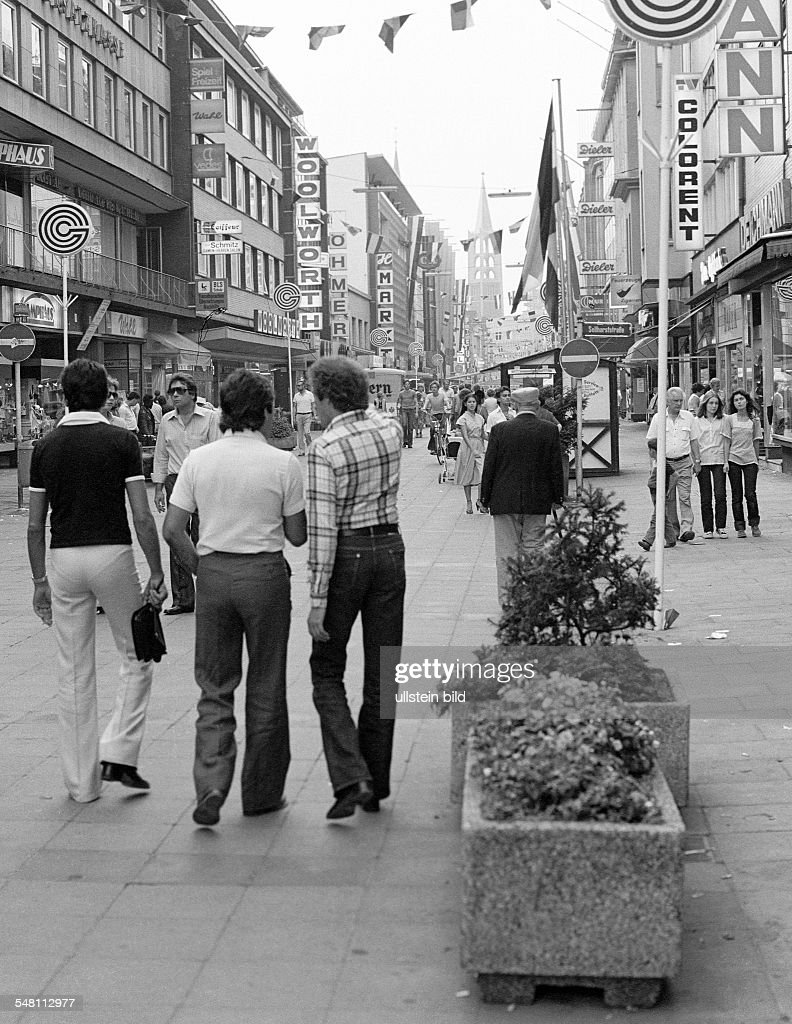 people on shopping expedition, three young men, aged 25 to 30 years, shopping street, pedestrian zone, Bahnhof Street, in the background the Evangelic City Church, D-Gelsenkirchen, Ruhr area, North Rhine-Westphalia - 31.08.1979 : News Photo