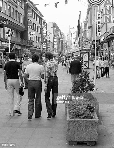 People on shopping expedition, three young men, aged 25 to 30 years, shopping street, pedestrian zone, Bahnhof Street, in the background the...