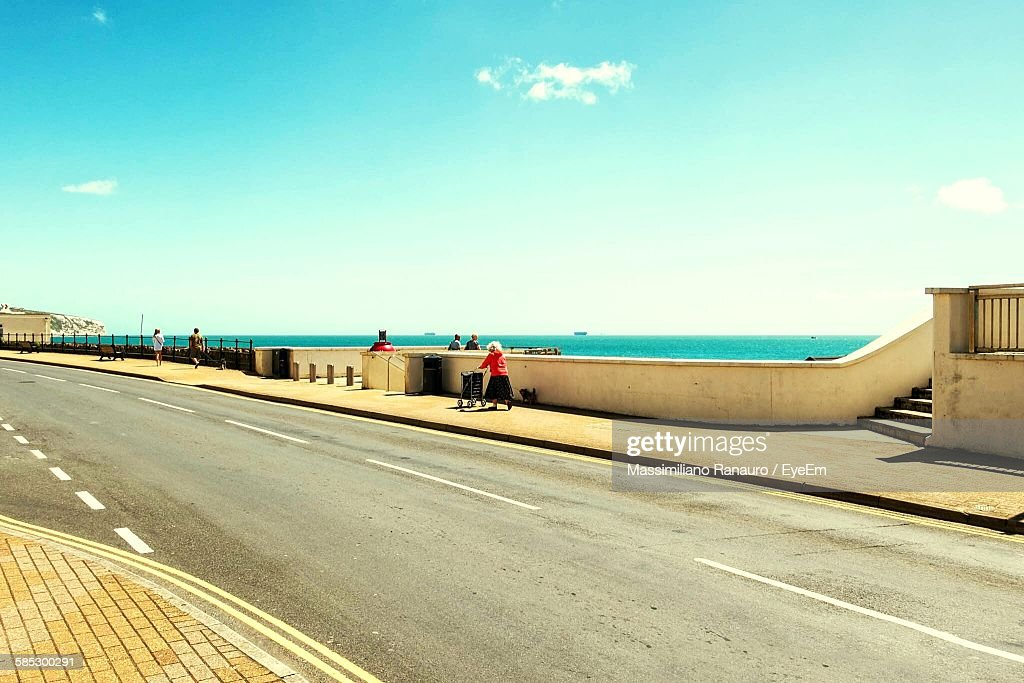 People On Sidewalk Against Sky At Isle Of Wight : Stock Photo