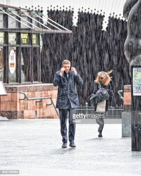 people on sidewalk against train station entrance - heavy rain stock photos and pictures