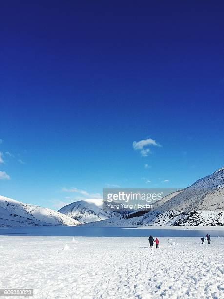 People On Snow Covered Field By Mountains Against Blue Sky