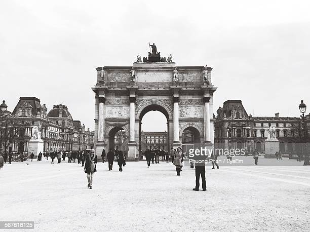 people on snow covered field in front of arc de triomphe du carrousel against clear sky - arc de triomphe du carrousel stock photos and pictures