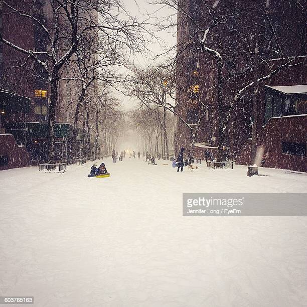 People On Snow Covered Street In City