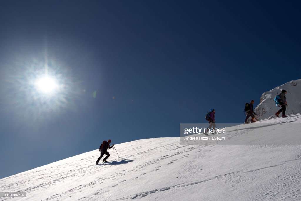 People On Snowcapped Mountain Against Sky During Winter : Foto de stock