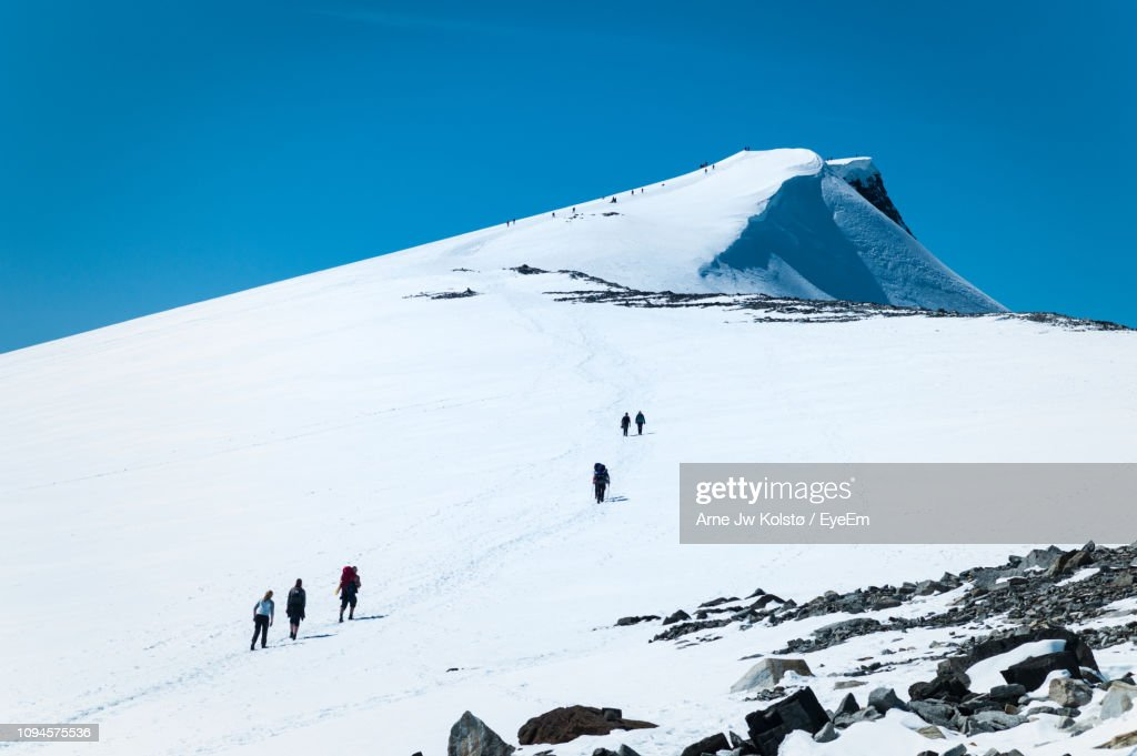 People On Snowcapped Mountains Against Clear Blue Sky : Stock Photo