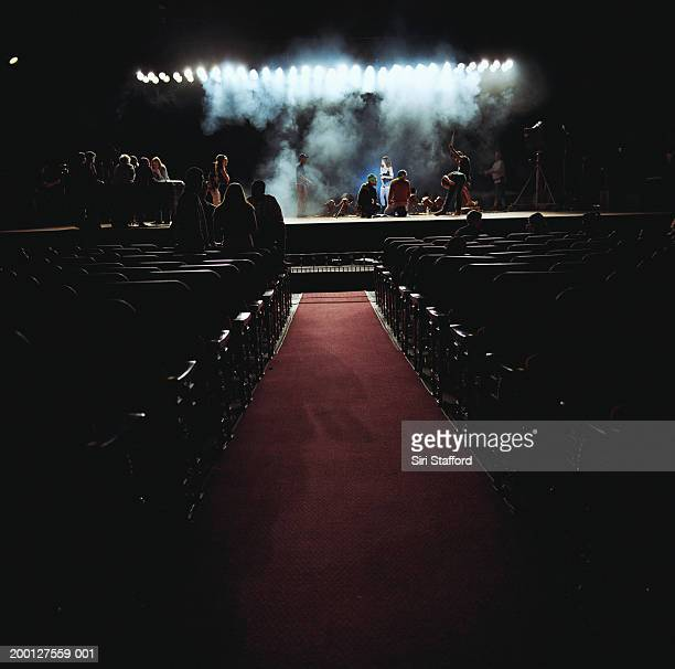people on stage in empty theater, preparing for event - red carpet event photos et images de collection