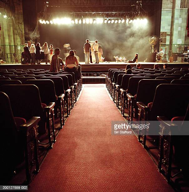 People on stage in empty theatre, waiting for event