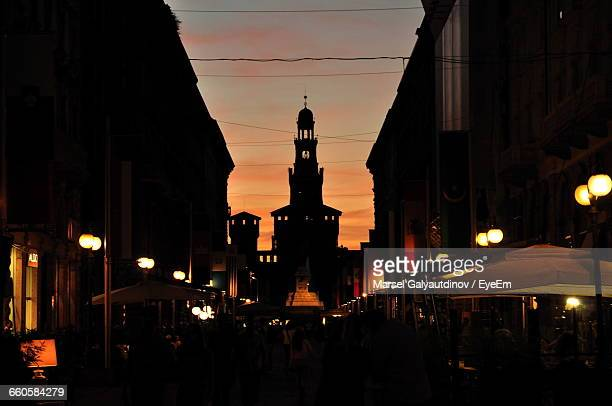 People On Street Against Silhouette Castello Sforzesco During Sunset In City