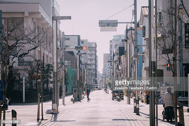 people on street amidst buildings in city - road signal stock pictures, royalty-free photos & images