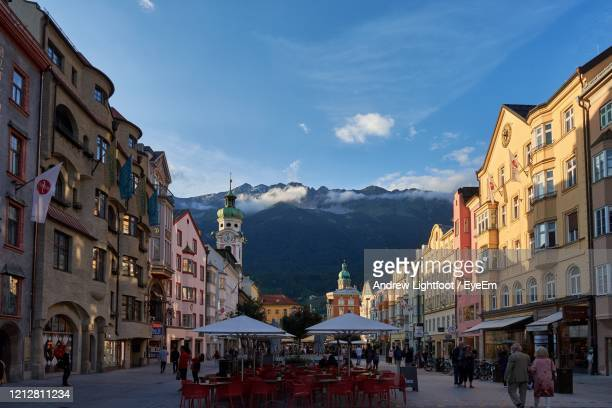 people on street amidst buildings in city with mountains in background - innsbruck stock pictures, royalty-free photos & images