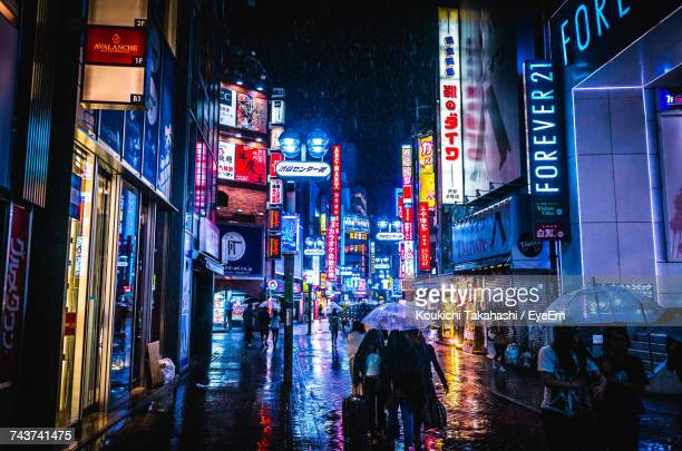 People On Street Amidst Illuminated Buildings During Rainy Season At Shibuya