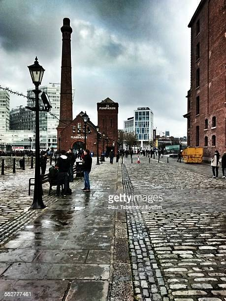 people on street by albert dock against cloudy sky - merseyside stock pictures, royalty-free photos & images