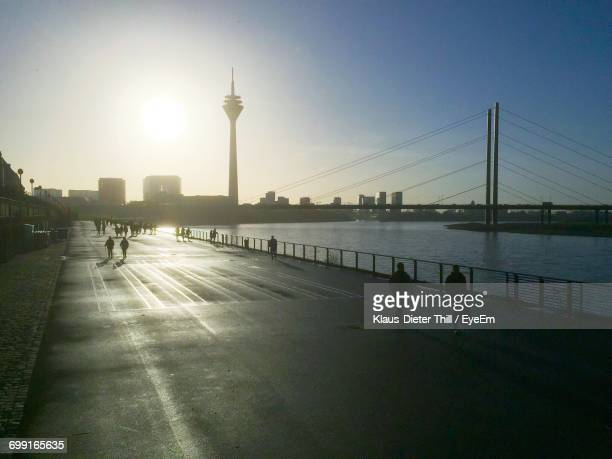 People On Street By Rhine River In City Against Sky