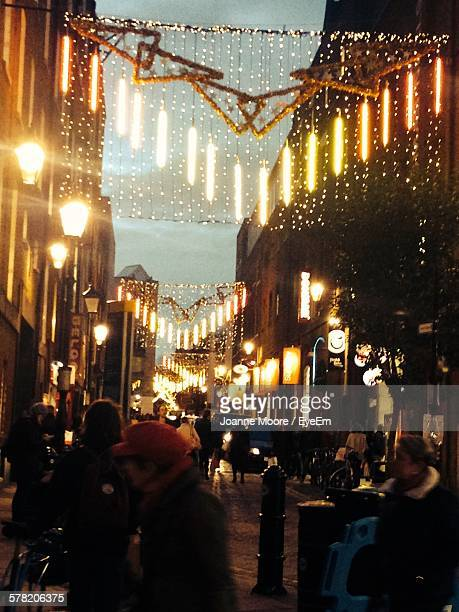 People On Street With Christmas Lights At Night