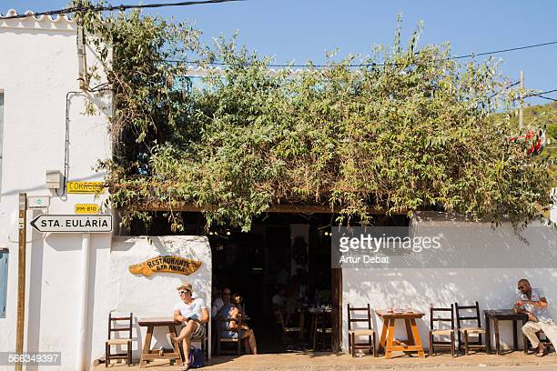 People on the bar terrace with summer light on the white architecture of the Ibiza island