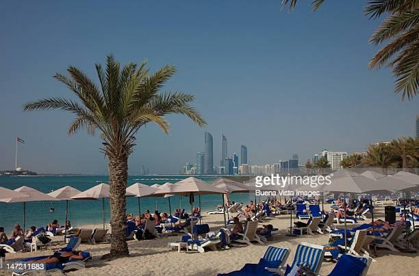 People on the beach and Abu Dhabi skyline