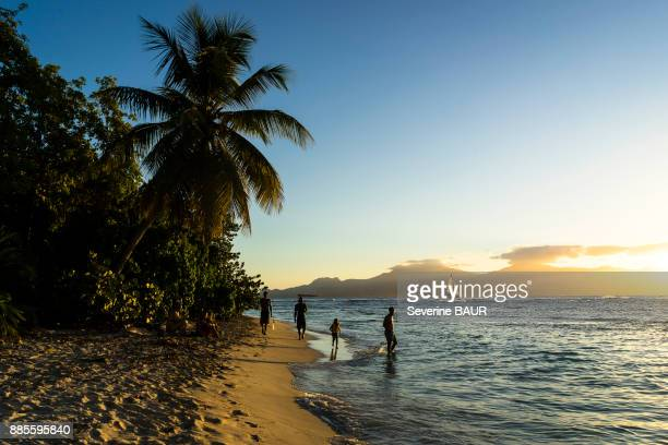 People on the beach at the sunset, Gosier island, Guadeloupe, France