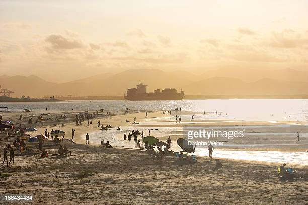 CONTENT] People on the beach enjoying the sunset and a big ship sailing on the sea Praia do Forte