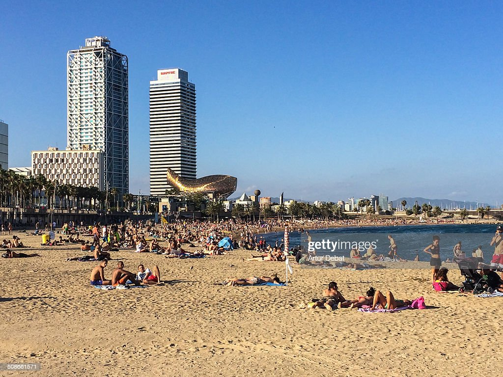 People on the beach of Barceloneta in Barcelona's city taking sunbath with the Mapfre towers on the background.