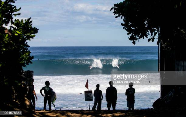 People on the beach watch Hawaii's Lucas Godfrey surf Backdoor Pipeline after the Volcom Pipe pro on the north shore of Oahu on February 6 2019 /...