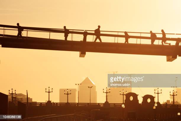 people on the bridge against sky at sunrise - canary wharf stock pictures, royalty-free photos & images