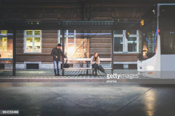 people on the bus stop on a rainy night - waiting stock pictures, royalty-free photos & images