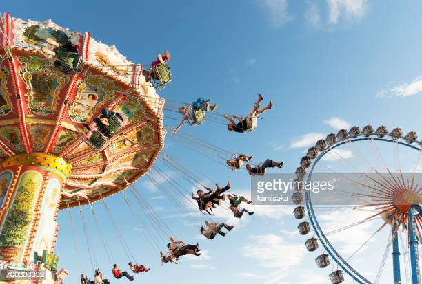 people on the chain carousel at oktoberfest - munich stock pictures, royalty-free photos & images