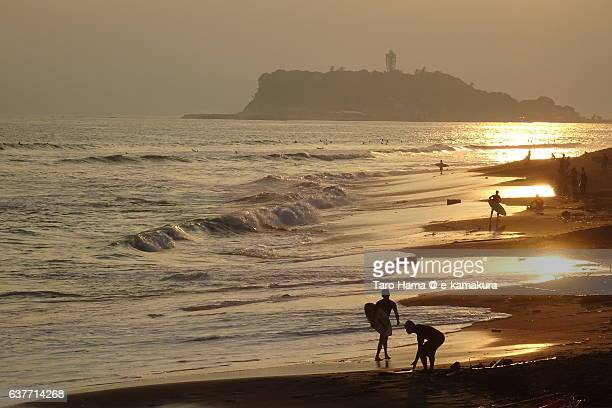People on the golden colored sunset beach