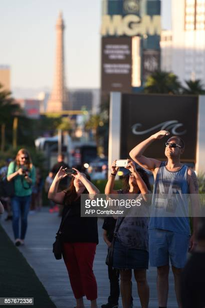 People on the Las Vegas Strip October 4 stop to photograph the two broken window in the Mandalay Bay hotel from which killer Stephen Paddock let...