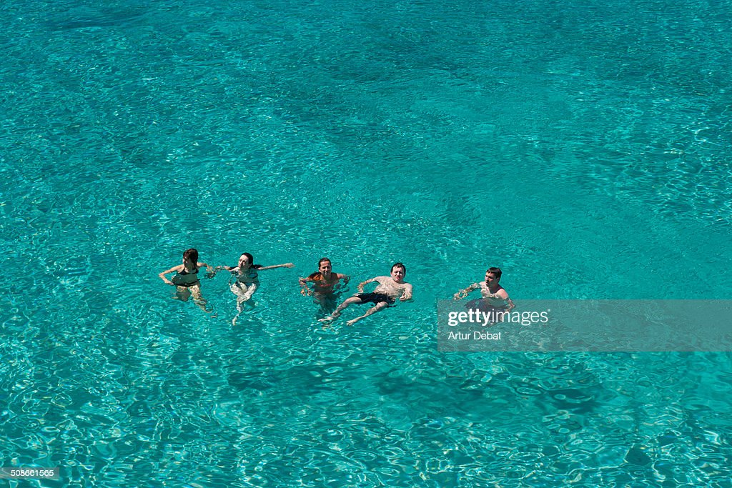 People on the Minorca's crystal water beach view from above in summer vacations.