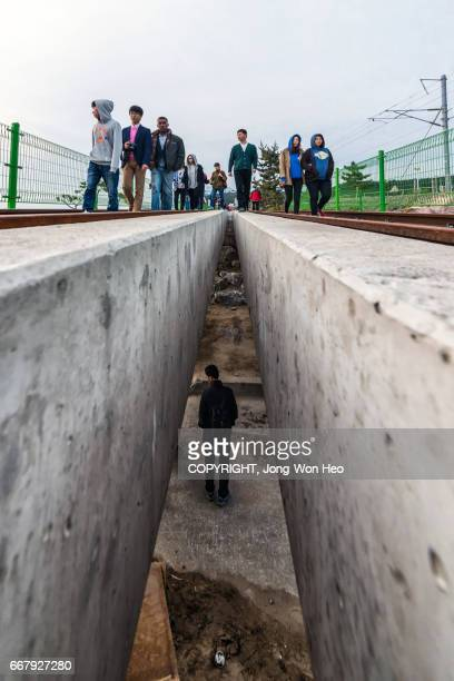 People on the railroad track and a man under the track