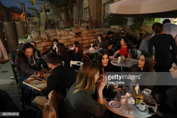 People on the southern Greek side of the divided city sit at an outdoor cafe next to sandbags and barrels that create a small fortification at the...