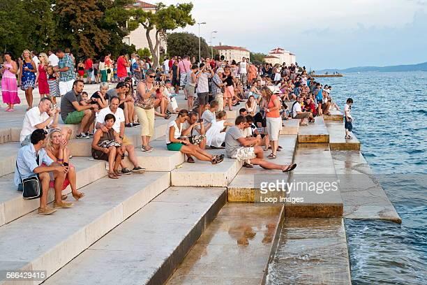 People on the steps of the Sea Organ in Zadar on the Adriatic coast of Croatia