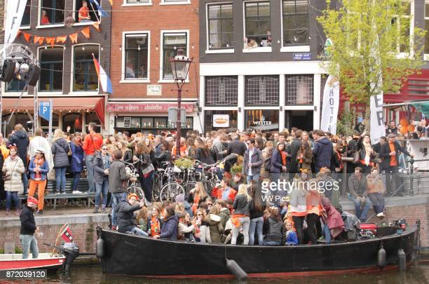 People on the street and boats at Prinsengracht canal celebrate King's Day in AmsterdamNetherlands on April 27 2017 The King's day marking the birth...