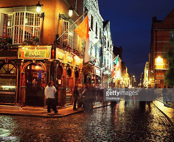 people on the street in temple bar in dublin, ireland - temple bar dublin stock photos and pictures