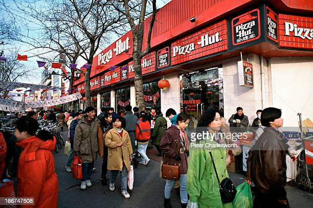 People on the street outside of a large Pizza Hut restaurant