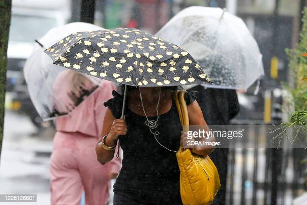 People on the streets, shelter themselves from rain underneath umbrellas as Storm Ellen brings heavy rainfall with gusty winds in north London....