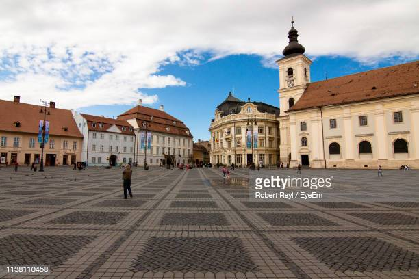 people on town square against buildings in city - sibiu stock photos and pictures