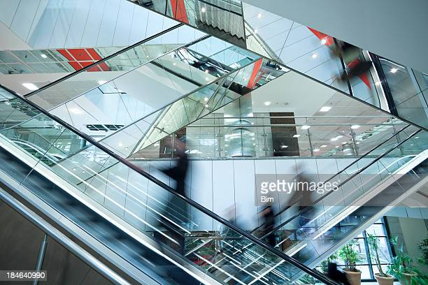 people on two crossed escalators, blurred motion - shopping mall stock pictures, royalty-free photos & images