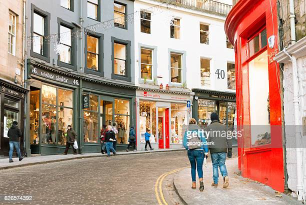 people on victoria street in edinburgh's old town - edinburgh scotland stock photos and pictures