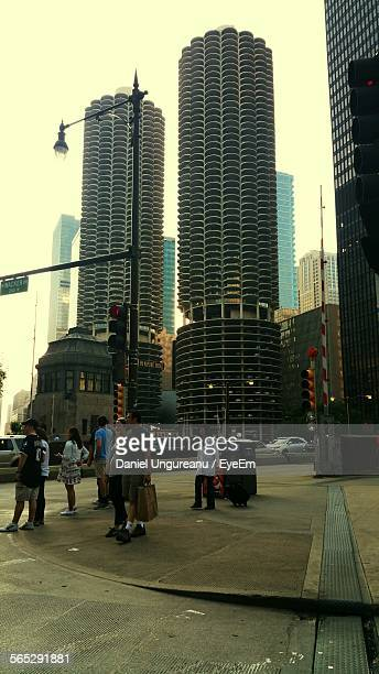 People On Walkway In Front Of Modern Marina Towers Against Sky