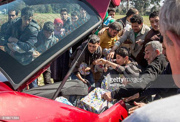 People open the boot of car as it is being driven away by a man trying to distribute aid at the Idomeni refugee camp on the Greek Macedonia border on...